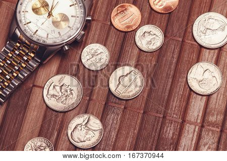 Luxury but not new watch with coins. Cost-is-no-object time is money poor income concept. Vintage tone image
