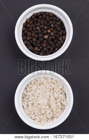 Course Gray Salt And Peppercorns In Smal Ramekins On Matte Black Surface