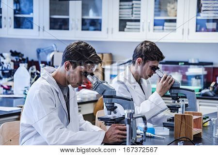 A young medical or scientific researcher or doctor using looking at a microscope in a laboratory with his colleague.