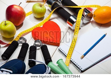 Heart, dumbbells and fruits, apples, oranges on a white wooden background