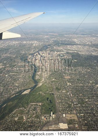 Aerial view of downtown Calgary Alberta in summer with airplane wing tip river streets and buildings. Yellow canola fields with haze on horizon in background.