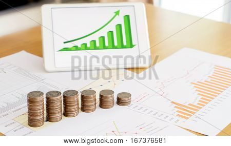 Grow up coins stack with business and finance graph screen on laptop computer on desk of investor adviser. Concept of financial and investment growth.