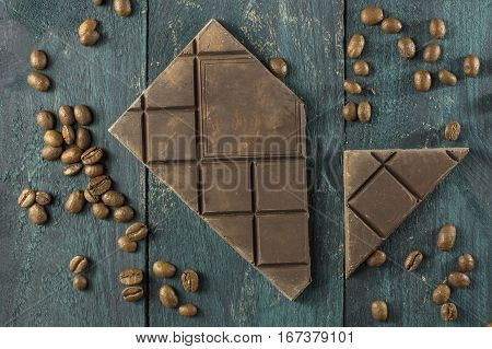 Artisan chocolate with coffee grains on a dark wooden boards texture