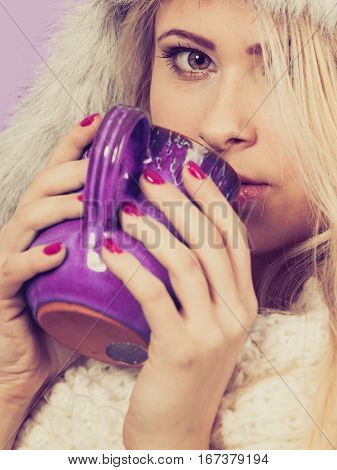 Clothing accessories seasonal clothes concept. Woman wearing red jumper and winter furry warm hat holding and drinking hot drink from mug