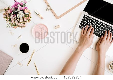 Top view office desk. Workspace with girl's hands laptop wildflowers bouquet coffee cup golden pen and clips clipboard. Flat lay