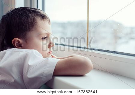 Sad Little Boy Sitting Near The Window