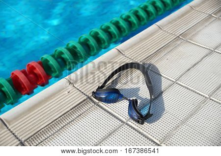 Blue goggles for swimming on a side of the swimming pool