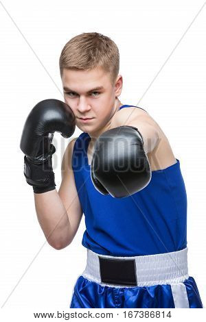 Young handsome left-hander boxer sportsman in blue boxer suit and black gloves standing on white backgound. Isolated. Copy space.