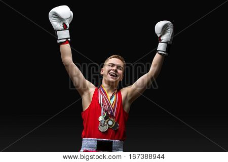 Happy young handsome boxer sportsman in red boxer suit and white gloves with medals standing on black backgound. Winner. Copy space.