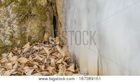 Large ice flow on the side of a hill with leaves and twigs on the ground and green moss on the side of a stone