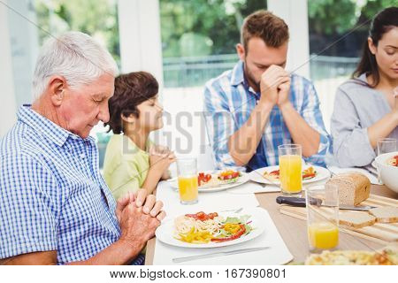 Multi generation family praying while sitting at dining table in home