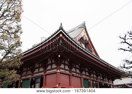 In the picture we can see a red colored temple in a pagoda style. There are some trees around the temple some of them can be seen in the picture.