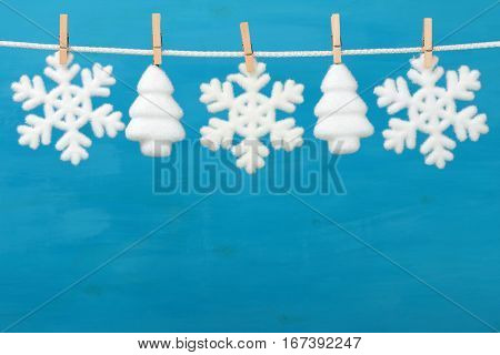 Christmas baubles in shape of snowflake and spruce on blue wooden background