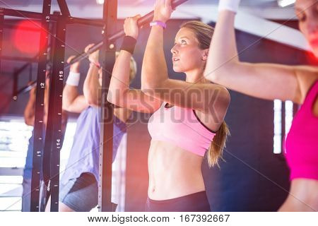 People doing chin ups exercise while hanging in gym