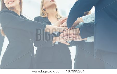 closeup of business team standing in a circle shaking hands with each other.