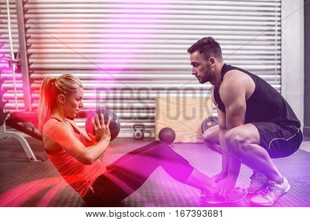 Fit couple doing abdominal ball exercise at crossfit gym