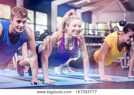 Fit people exersicing in plank position at gym