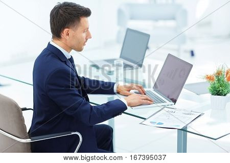 accountant was sitting at the table in front of the open laptop. On the screen of the laptop - financial charts. on the table laid out financial documents