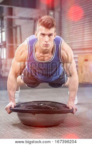 Muscular man doing push up on bosu ball at crossfit gym