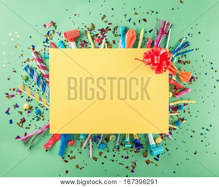Big card with various party confetti balloons streamers noisemakers and decoration. Colorful celebration background. Top view. Flat lay