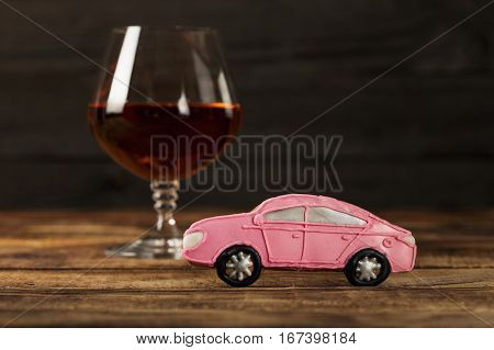 Small baby car with a glass of brandy on a wooden table. The concept of the social problem of drunk driving