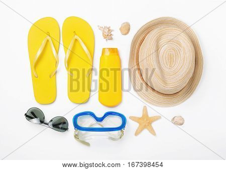 Variety beach accessories on white background. Vacation and travel items top view