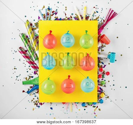 Balloons with different smiles and various party confetti streamers noisemakers and decoration on a white background. Colorful celebration background. Top view. Flat lay