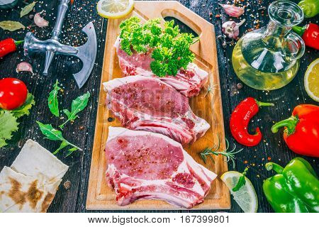 Raw porkchops with vegetable and spices on the dark wood