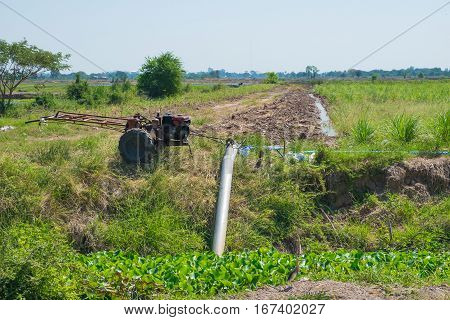 Farmers Pumping water to Jasmine rice fields with old tractor drought concept