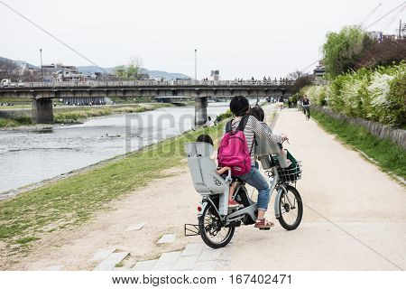 In the picture we can see a woman riding a cycle by taking her two babies one in the front and another baby on the rear seat. Few plants, trees and a bridge are also seen in the picture.