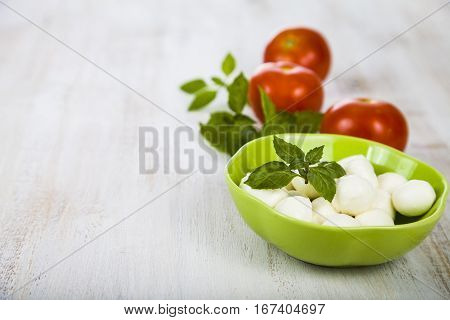 Mozzarella in a green plate on a wooden table. Mozzarella balls with basil leaves and tomato on a wooden board. Ingredients for caprese salad.