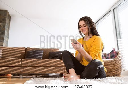 Beautiful young happy woman at home sitting on carpet with legs crossed, holding smart phone, texting