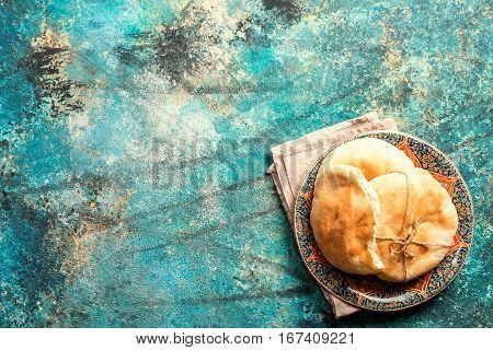 Pita or Arabic bread on blue background, top view with copy space