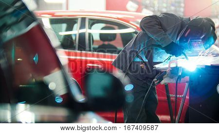 Industrial concept: worker in helmet repair detail in car auto service, telephoto
