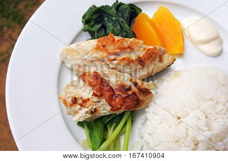 Indigenous Fijian seafood and vegetables dish served in a plate. Fried fish with papaya rice and steamed pumpkin leaves.