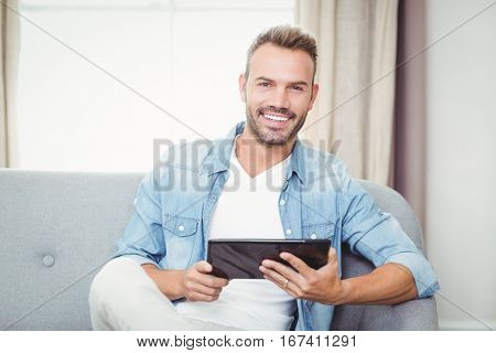 Portrait of cheerful man holding digital tablet at home