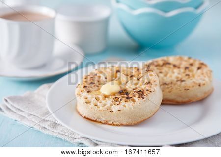 Two toasted crumpet on the blue table, selective focus