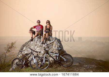 Couple Cyclists Sitting On Stone Near Bicycles In The Evening