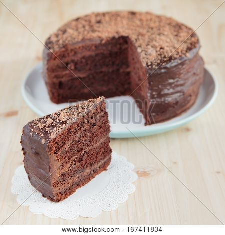 Piece of chocolate cake on the wooden table, square