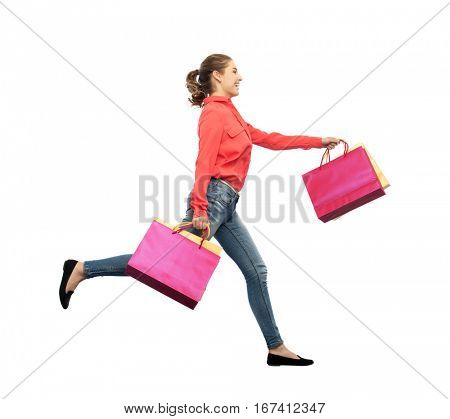 sale, motion and people concept - smiling young woman with shopping bags running in air over white background