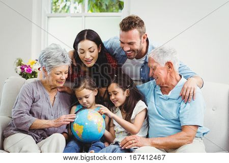 Happy family on sofa looking at terrestrial globe