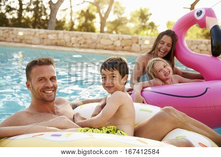 Family On Vacation On Inflatables In Outdoor Swimming Pool