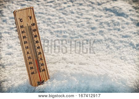 Wooden Thermometer in the snow with freezing temperatures. vignetting as an artistic effect