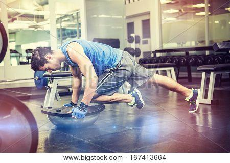 Muscular man exercising with bosu ball in gym