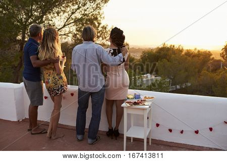 Two couples admire view from rooftop at sunset, full length