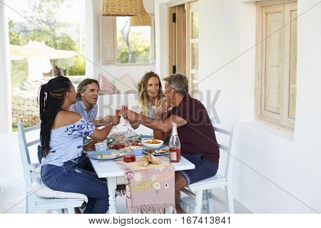 Couples dining on a patio look at each other and make a toast