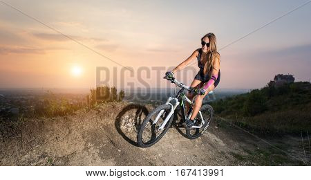 Girl Riding On The Mountain Bicycle Against Evening Sky