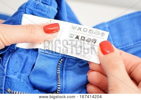 Woman checking the care label of a pair of blue jeans