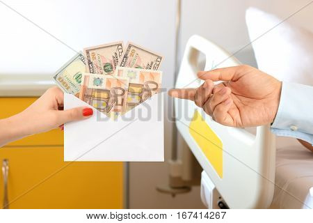 Woman bribing a man with an envelope full of money on a hospital bed suggesting a corrupt healthcare system