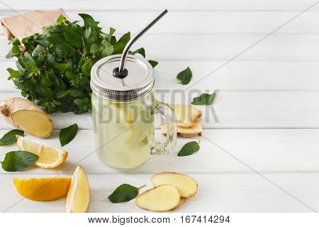 Detox cleanse drink, natural lemonade ingredients. Organic healthy juice in glass jar for weight loss diet or fasting day. Mint, lemon and ginger mix on white wood with copy space poster